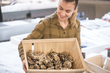 Woman in the supermarket with oysters. Beautiful young woman is holding a large box of oysters. The concept of healthy eating. Seafood