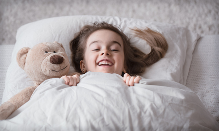 Cute little girl sleeps sweetly in a white cozy bed with a soft bear toy, the concept of children's rest and sleep Archivio Fotografico - 121012212