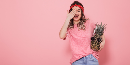 Horizontal portrait of hipster girl in stylish clothes, with closed eye and pineapple in her hands, on a pink background, lifestyle concept