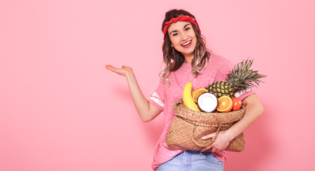 Horizontal portrait of hipster girl in stylish clothing, with bag with fruit, on pink background, lifestyle concept