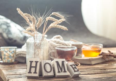 Stilllebendetails der Inneneinrichtung auf einem Holztisch mit Buchstaben nach Hause, das Konzept von Gemütlichkeit und Wohnatmosphäre. Wohnzimmer atmosphere Standard-Bild