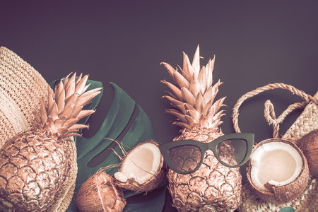 Summer tropical background with Golden pineapple and summer accessories with glasses, on a matte black background, the concept of creativity and style