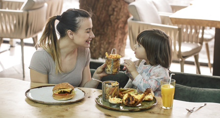 Loving family. Mom with cute daughter eating fast food in a cafe, family and nutrition concept Stock fotó
