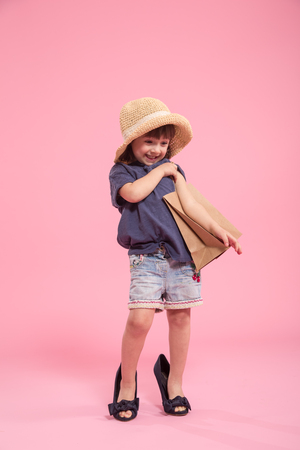 Funny little girl cute girl in summer hat with shopping bag and in the shoes of a mother, the concept of children's fashion, Studio shot isolated on pink background