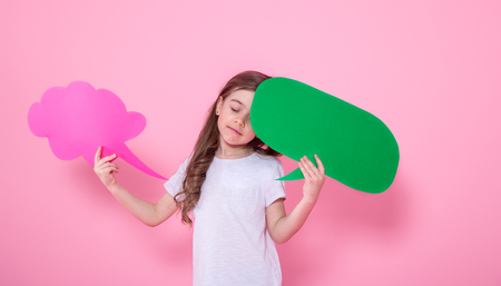 Cute little girl with speech icon on pink background .The concept of communication and communication . Studio shooting Stockfoto