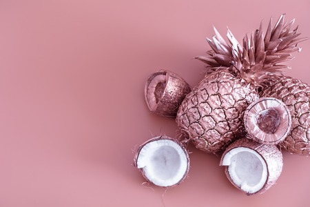 painted in gold fruit pineapple and coconut on a colored background, creative advertising design.Top view