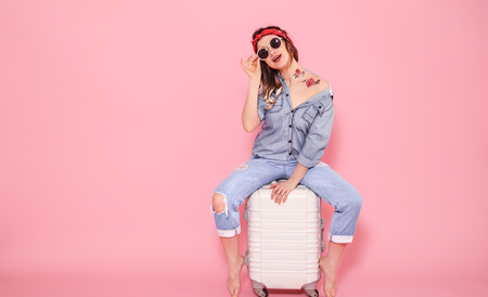 Horizontal portrait of a stylish girl in sunglasses and denim clothes with a tattoo on her body, sitting on a white suitcase on a pink background, concept of lifestyle and travel