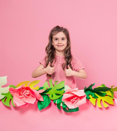 一个小女孩的肖像在夏季粉红色的背景用纸花,文字的地方,夏季广告概念