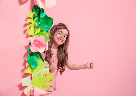 Little cute girl on color background with paper flowers , place for text, summer advertising concept Stockfoto