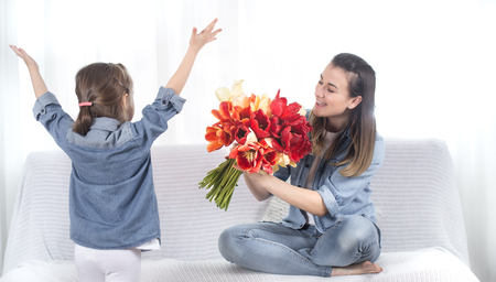 Happy mother's Day. Little sweet daughter with a large bouquet of tulips congratulates her mother. In the interior of the living room, the concept of a happy family life Imagens - 122412065