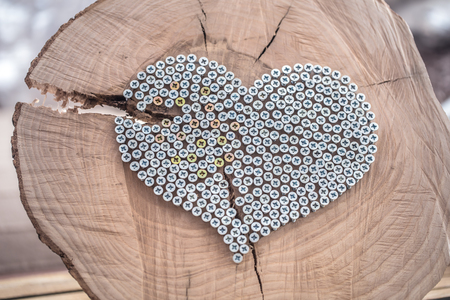 decorative heart of nails on a wooden background in the interior of the room . The concept of home comfort and design