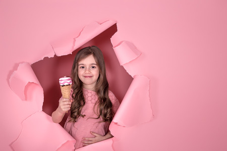 funny little girl peeking out of the hole with ice cream in her hands, on a colored pink background, space for text, Studio shooting