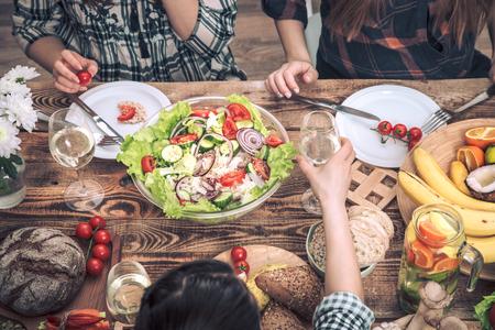 Das Abendessen mit meinen Freunden genießen. Draufsicht auf eine Gruppe von Menschen, die zusammen speisen, an einem rustikalen Holztisch sitzen, das Konzept der Feier und gesunde Hausmannskost