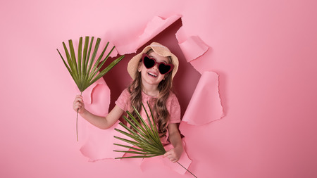 funny little girl looks out from the hole in a beach hat and glasses in the shape of a heart, in the hands of tropical leaves, on a colored background, a place for text, Studio shooting