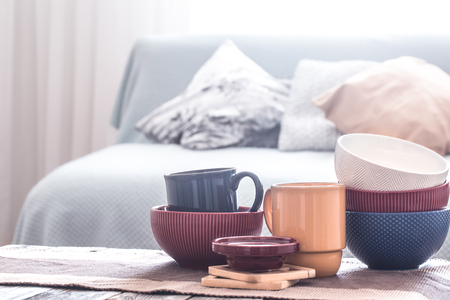 still life interior decor with home utensils on a wooden table , on the background of a sofa with pillows, the concept of home comfort