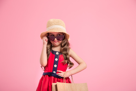 little fashionista with a shopping bag in summer hat and sunglasses , colorful pink background , the concept of childrens fashion 版權商用圖片