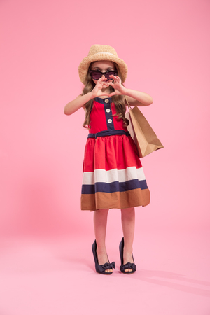 little fashionista with a shopping bag in a summer hat and glasses , on a colored pink background in moms shoes , the concept of childrens fashion