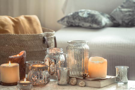 Still-life. Home cozy beautiful decor in the living room, vase and candles, on the background of a wooden table, interior details concept