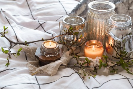 Home interior. Cozy still life with different candles in bed and spring flowers