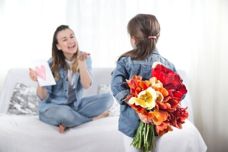 Happy mothers Day. Little sweet daughter with a large bouquet of tulips congratulates her mother. In the interior of the living room, the concept of a happy family life