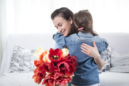 Happy mother's Day. Little cute daughter hugs her mother , and gives a bouquet of tulips, close-up photo. In the interior of the living room, the concept of a happy family life Imagens