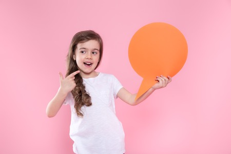 Cute little girl with speech icon on pink background .The concept of communication and communication . Studio shooting 版權商用圖片