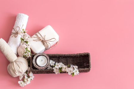 Spa still life on a pink background with spring flowers and organic body care products. The concept of Spa body care