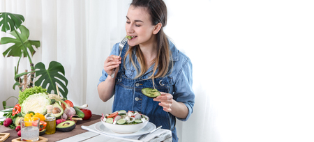 Young and happy woman eating salad at the table ,on a light background in denim clothes. The concept of a healthy home-made food. Place for text .