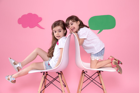 Two little girls on a colored pink background are sitting on chairs with speech icons . The concept of communication and friendship