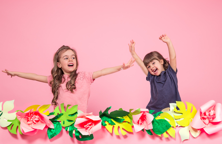 Portrait of two little girls on summer pink background with paper flowers, place for text, summer advertising concept. Two fashion sisters posing.