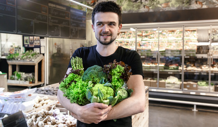 Young man in black t-shirt buying only green vegetables at the market