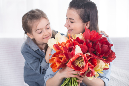 Happy mother's Day. Little cute daughter hugs her mother , and gives a bouquet of tulips, close-up photo. In the interior of the living room, the concept of a happy family life