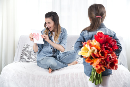 Happy mother's Day. Little sweet daughter with a large bouquet of tulips congratulates her mother. In the interior of the living room, the concept of a happy family life