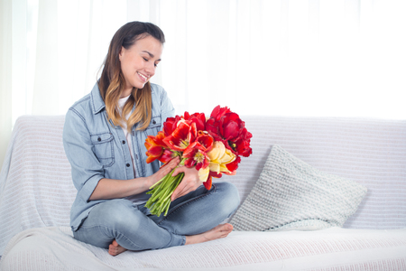 A young girl with a large bouquet of tulips sitting on the couch in the living room . Stock Photo