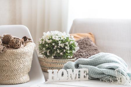 Stillleben im Wohnzimmer mit Holzaufschrift nach Hause, das Konzept des Wohnkomforts Standard-Bild