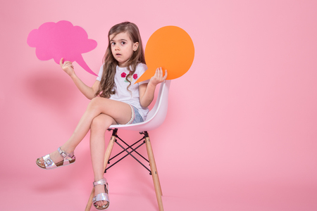A cute little girl with a speech icon on a pink background sits on a chair .The concept of communication