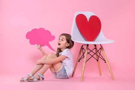 Cute little girl with a speech icon in her hands on a colored background, sitting near a chair with a big red paper heart .The concept of communication . Studio shooting