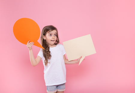 Cute little girl with speech icon on pink background .The concept of communication and communication . Studio shooting Foto de archivo - 124816816