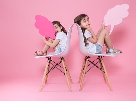 Two little girls on a colored pink background are sitting on chairs with speech icons . The concept of communication and friendship Foto de archivo - 124819510