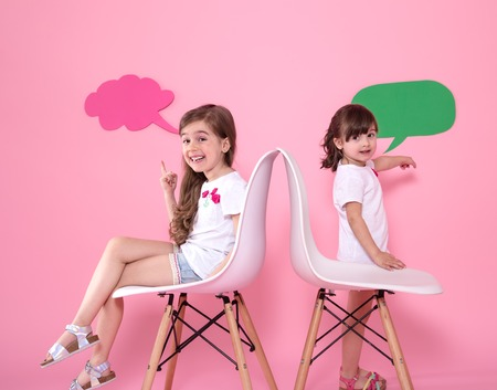 Two little girls on a colored pink background are sitting on chairs with speech icons . The concept of communication and friendship Foto de archivo - 124819512