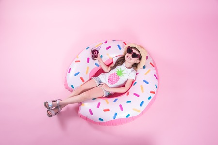 A little child girl in casual wear lying on a donut inflatable circle. Pink background. Top view. Summer concept. Stock Photo
