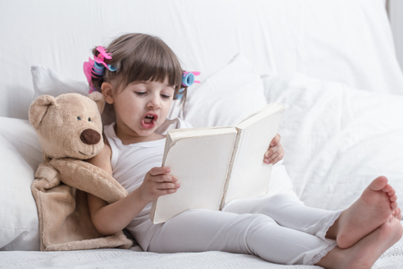 Cute little girl smiling while lying in a cozy white bed with , the concept of childrens rest and sleep Фото со стока