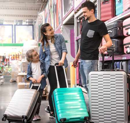 Positive couple with kid buying colourful suitcase on wheels for vacation in a big shopping mall Stock Photo
