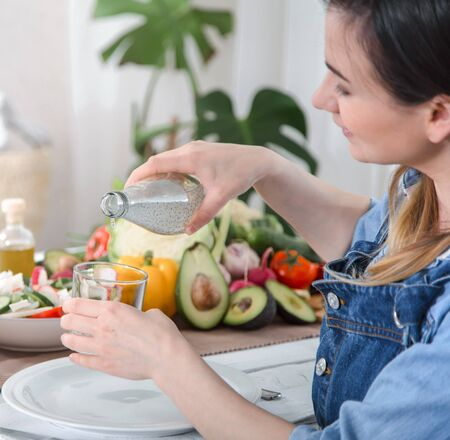 A young woman drinks water at a table with vegetables on a light background , dressed in denim clothes. Healthy food and drink concept .