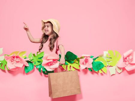 Portrait of cute little girl in summer hat , with shopping bag in hand on pink background with paper flowers, place for text, summer advertising concept Stock Photo