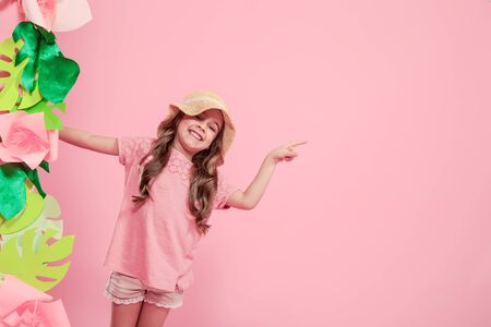 Little cute girl in summer hat on Color isolated pink background with paper flowers, place for text, summer advertising concept, Studio shooting