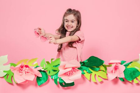 Portrait of little girl with heart shaped sunglasses on pink background with paper flowers, place for text, summer advertising concept