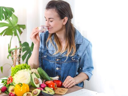 Young and happy woman eating salad with organic vegetables at the table on a light background , in denim clothes. The concept of a healthy home-made food.
