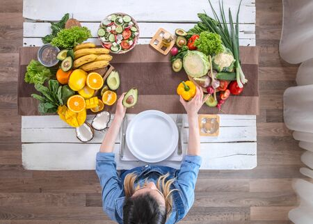 Woman at the dining table with a variety of organic healthy food , top view. The concept of healthy eating and celebration
