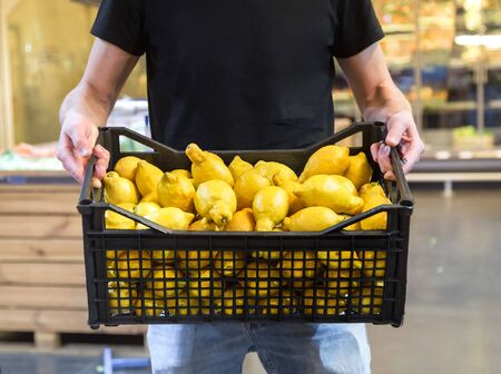 mother, husband and daughter choosing lemons in supermarket Stock Photo